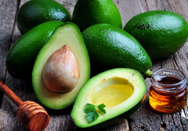 Fresh avocado with olive oil and honey on wooden background