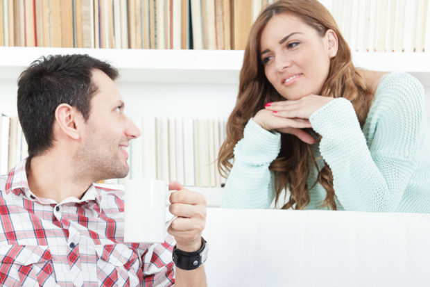 smiling woman listening carefully to her man, couple talking and listening to each other