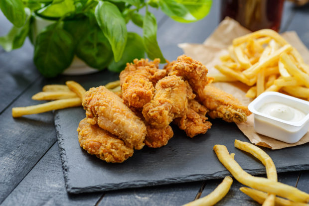 Fast Food Set - Fried Chicken, French Fries and Sauce on Black Slate.