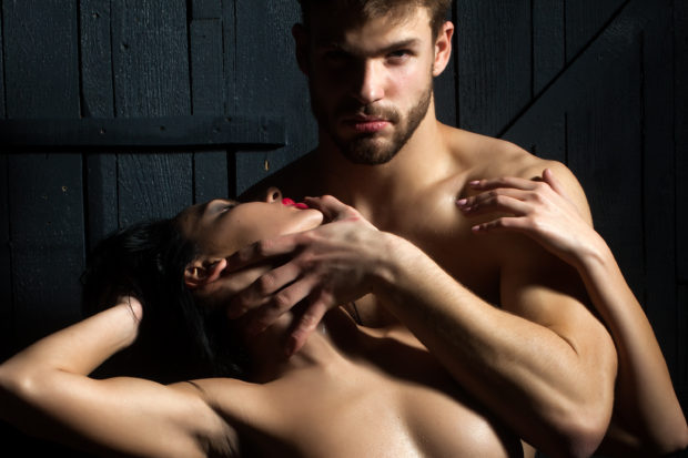 Young sexual undressed sensual attractive couple of handsome bearded muscular macho man touching and embracing passionate pretty woman with body and breast on studio background, horizontal picture