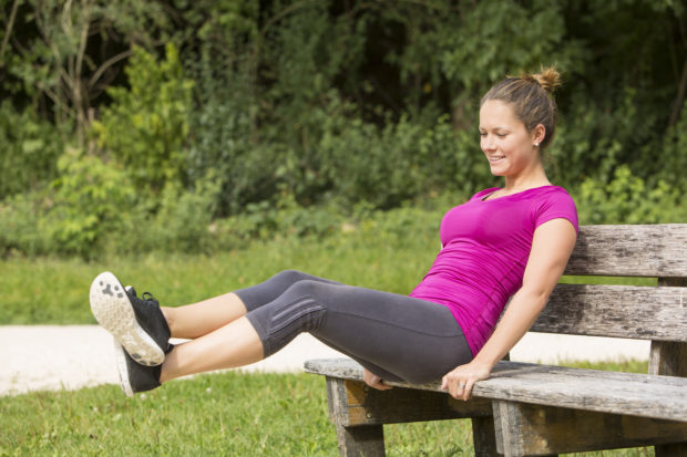 Sporty fit attractive young woman sitting on a wooden park bench doing leg lifts as she trains outdoors in the sunshine