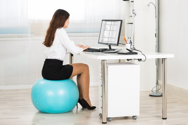 Side view of young businesswoman using computer while sitting on pilates ball in office