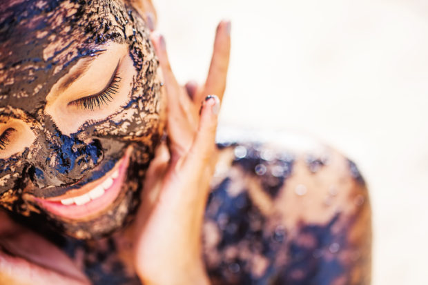 pretty asian girl applying chocolate face mask