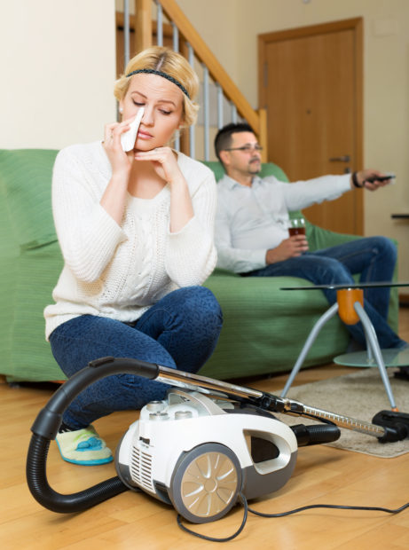 Upset woman with hoover looking at man on sofa watching TV