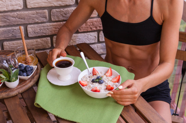 Fitness woman have a healthy breakfast. Healthy Homemade Oatmeal with Berries.
