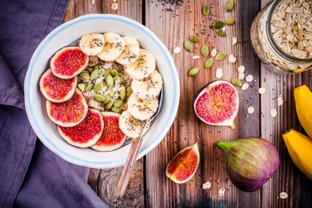 healthy breakfast: oatmeal with fresh figs, bananas, pumpkin seeds, coconut and chia seeds on wooden table