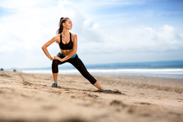 Fit woman doing exercises for legs on the beach on a sunny day