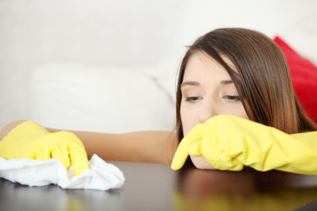 Tired young woman cleaning furniture table in yellow gloves