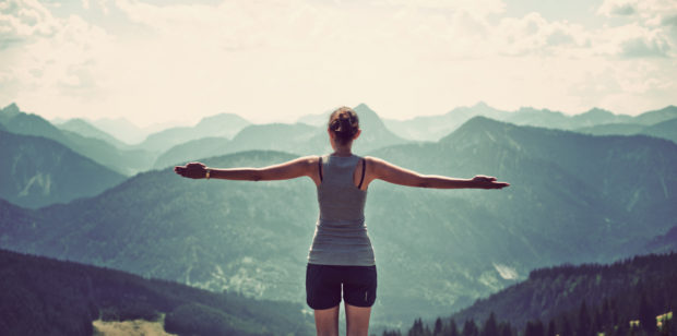 Woman celebrating nature and reaching the summit of a high mountain as she stands with her back to the camera and arms extended looking out over mountain ranges and valleys in a panoramic landscape