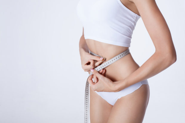 Healthy lifestyles concept. Woman measuring perfect shape of skinny body.