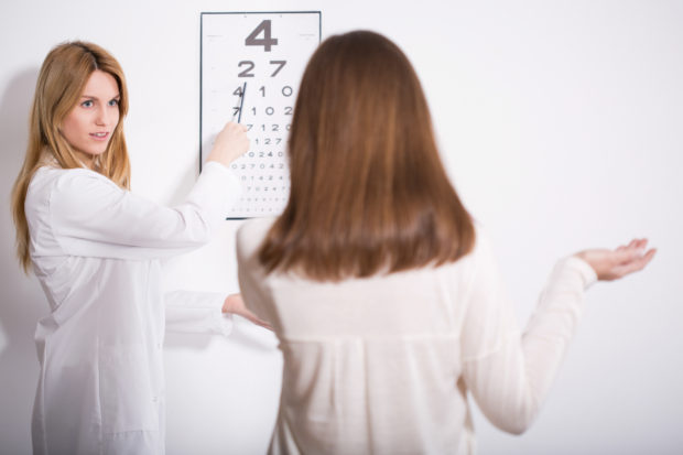 Woman suffering for myopia during eye exam
