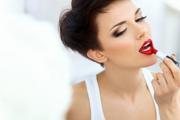 Beautiful Brunette applies lipstick. Lipgloss and Brush. Red lips Makeup