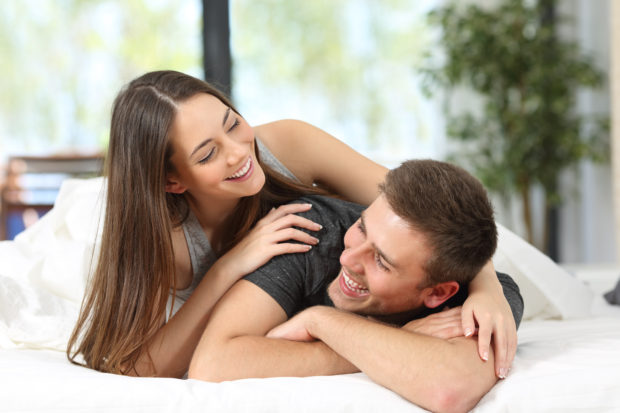 Portrait of a happy couple or marriage having fun and joking looking each other on the bed of an hotel room or home
