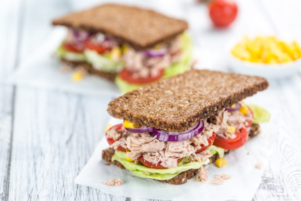 Tuna Sandwich (wholemeal bread; selective focus) on an old wooden table