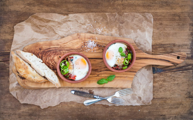Country style breakfast set. Eggs baked in separate clay cups with tomatoes, peppers, fresh basil, bread slices on rustic board over oily craft paper and wooden background, top view