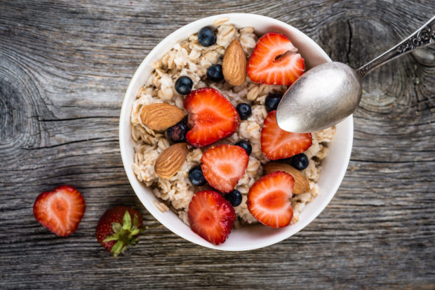 Oatmeal with almonds and berries in a bowl on wooden background. Top view. Diet breakfast.