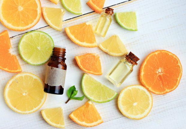Citrus essential oil. Various citrus fruit and aroma bottles. Orange, lime, lemon slices. Top view.