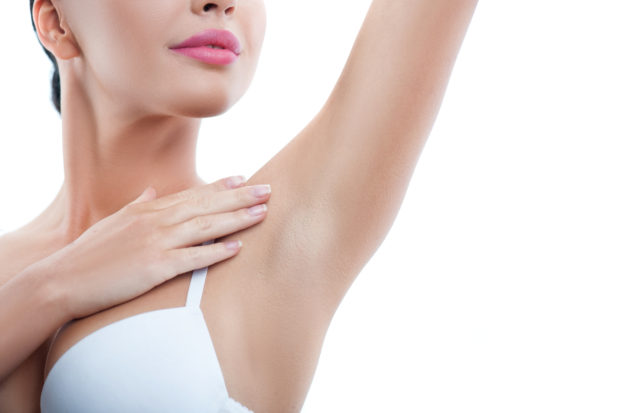 Cheerful girl is touching her smooth armpit with satisfaction. She is standing and raising her arm up. Isolated and copy space in right side